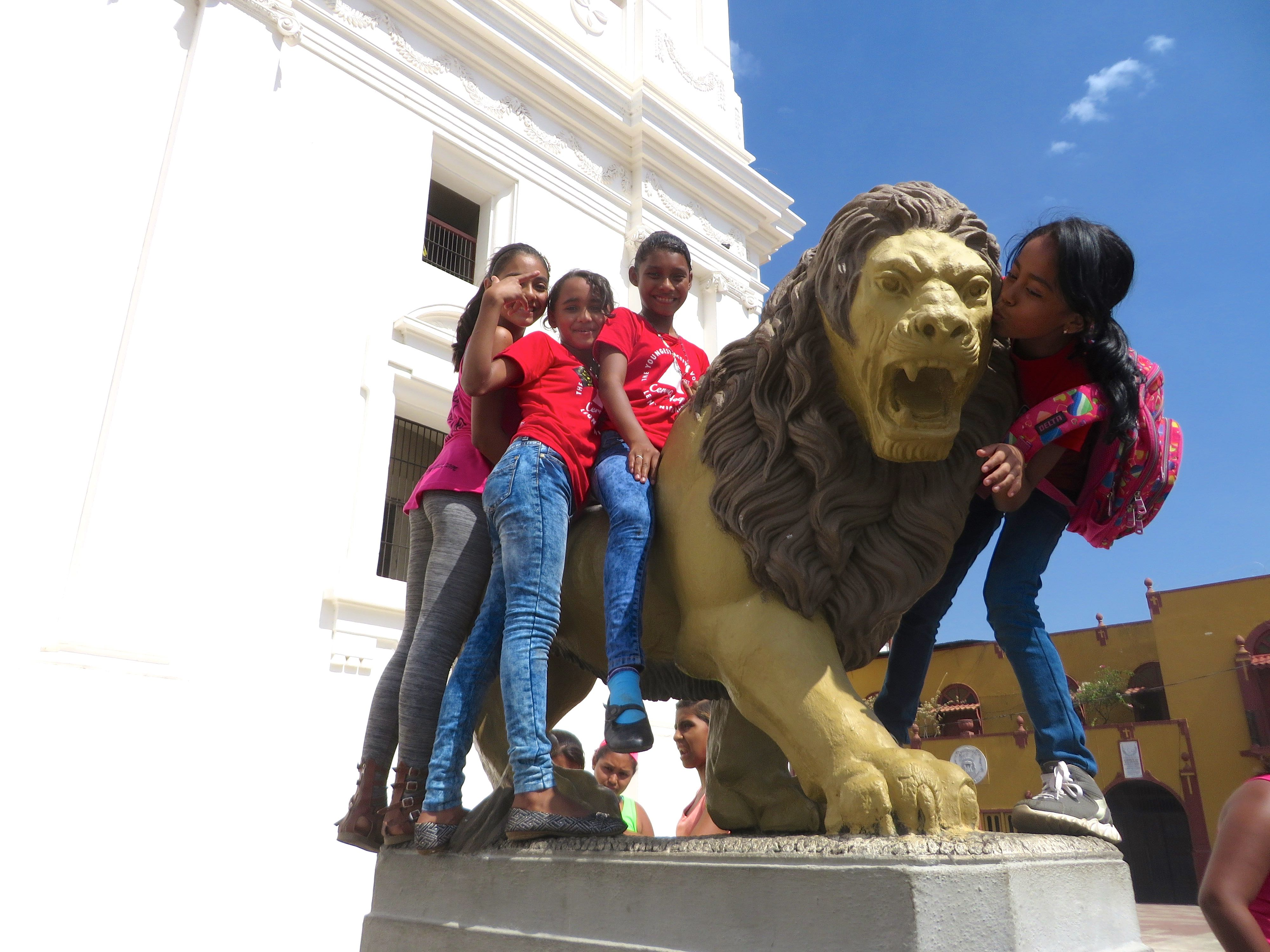 Jennifer, Makeyling, Maryuri and Grethel climbing the lion statue outside the cathedral.